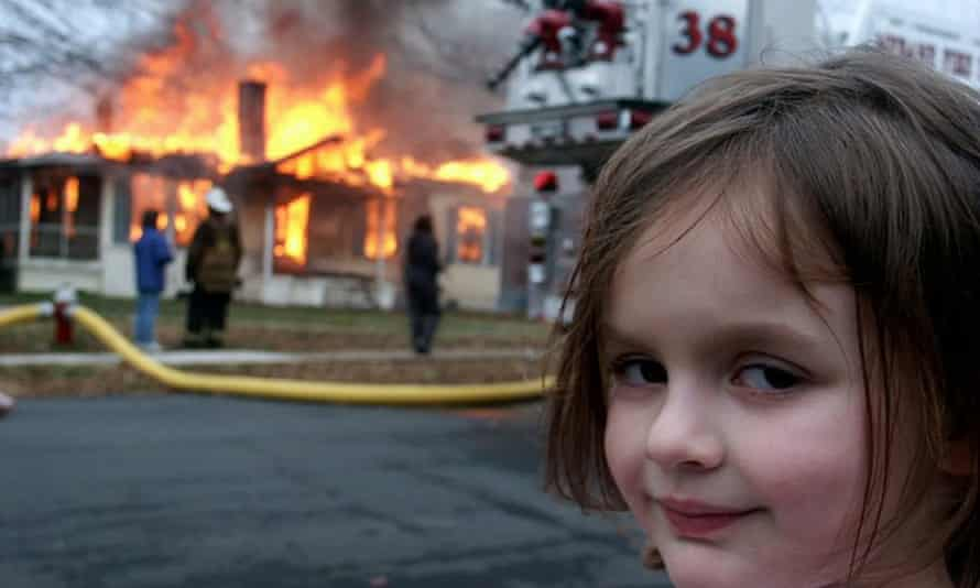 meme happy disaster girl standing next to the house on fire